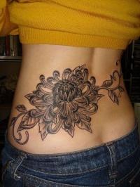 Big black flower tattoo on lower back